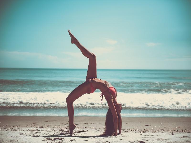 Žena cvičí jogu na pláži