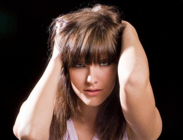 žena sa drží za vlasy